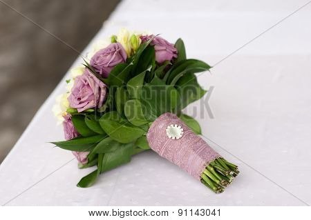 Bridal Bouquet Of Purple And White Roses On The Table