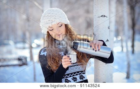Beautiful Brunette Pours Coffee From A Thermos For A Walk In Winter