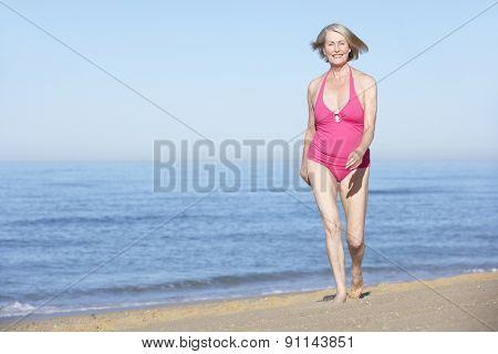Senior Woman Running Along Summer Beach