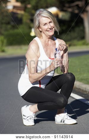 Senior Woman Resting And Drinking Water After Exercise