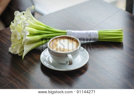 Wedding Bouquet Of Calla Lilies On A Table With A Cup Of Coffee