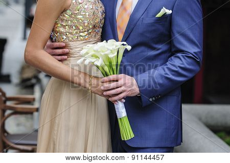 Bride And Groom Holding A Wedding Bouquet Of Callas