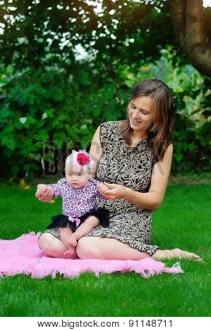 Family, Child And Parenthood Concept - Happy Mother Holding And Raising Little Baby Up In Park