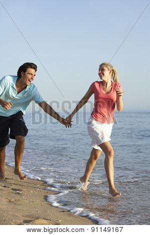 Young Couple Running Along Beach
