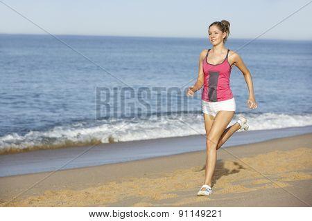 Young Woman Jogging Along Beach
