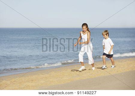 Children Running Along Sand On Beach Holiday