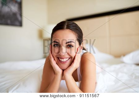 Woman Lying In Bed Resting Chin In Hands.