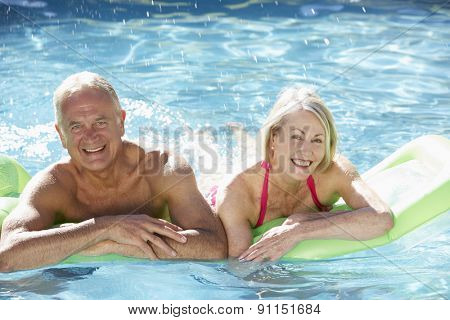 Senior Couple Relaxing In Swimming Pool On Airbed Together