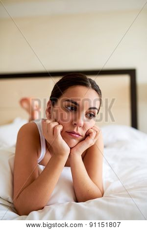 Woman Lying In Bed Looking Downcast.