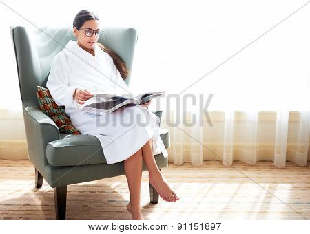 Woman Sitting In Chair Reading Book.