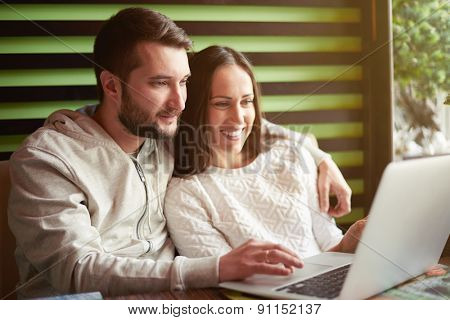 smiley young adult couple using laptop in restaurant