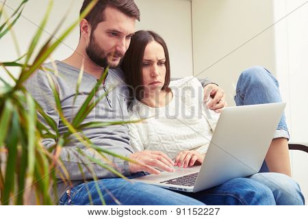 indoor photo of serious young adult couple holding laptop and looking at the screen