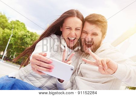 urban photo of laughing young couple showing peace sign and taking a selfie