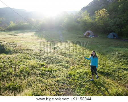 A Young Girl Walks On The Nature Near The Tents.