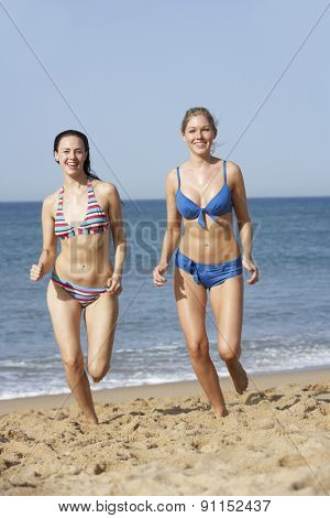 Two Women Wearing Bikinis Running Along Beach