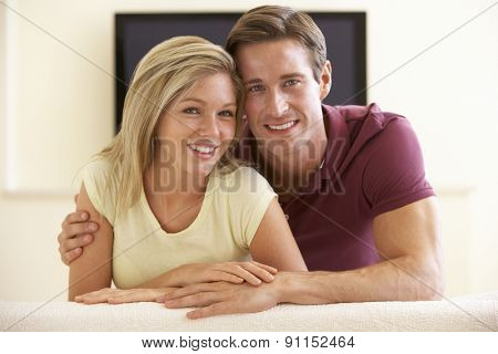 Couple Watching Widescreen TV At Home