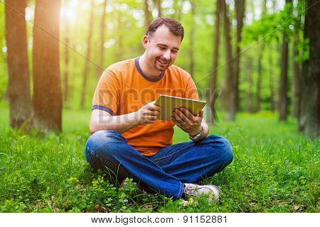 Man With Tablet In The Park