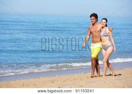 Young Couple Walking Along Summer Beach