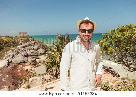 Smiling young man posing near ruins.