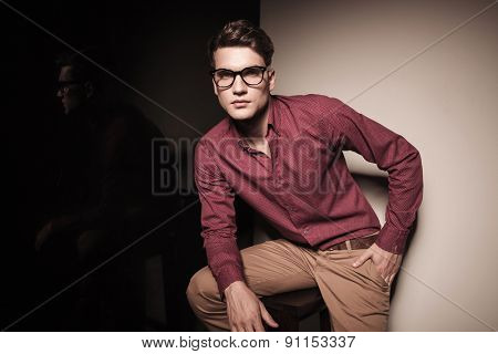 Handsome young casual man sitting on a stool resting his right hand on his leg.