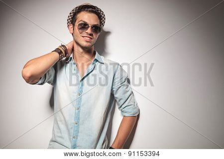 Young fashion man smiling and looking away while holding one hand to his neck.