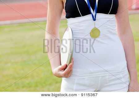 Close-up Of A Female Athlete With A Gold Medal Holding A Disc