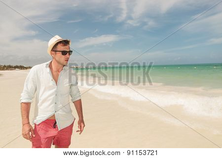 Handsome young man walking on the beach, looking at the sea.