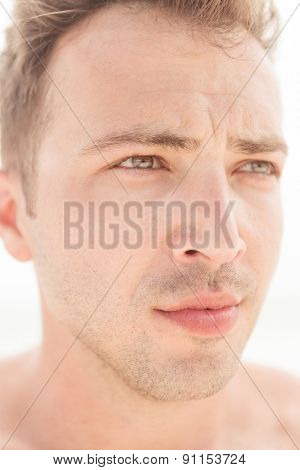 Close up picture of a young handsome man looking away from the camera.
