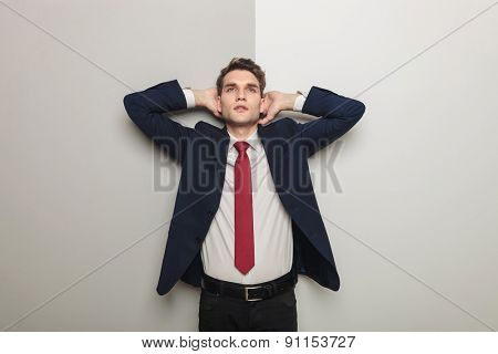 Young business man holding both hand to his head while leaning on a grey wall.