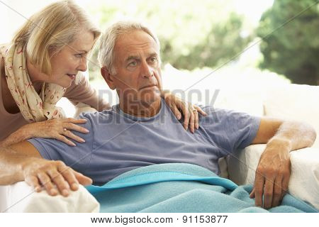 Wife Comforting Senior Man Feeling Unwell Resting Under Blanket