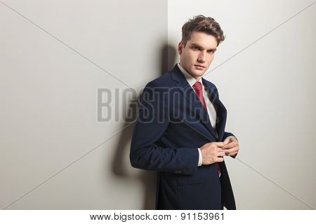 Handsome young business man closing his jacket while leaning on a grey wall.