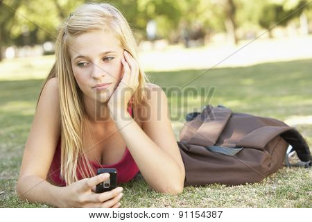 Unhappy Female Teenage Student With Mobile Phone In Park