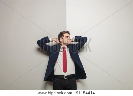 Picture of a young business man leaning on a grey wall holding both hand to his head while looking away from the camera.