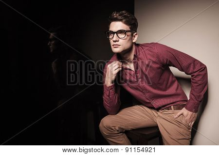 Attractive young casual man leaning on a stool while pulling his collar.