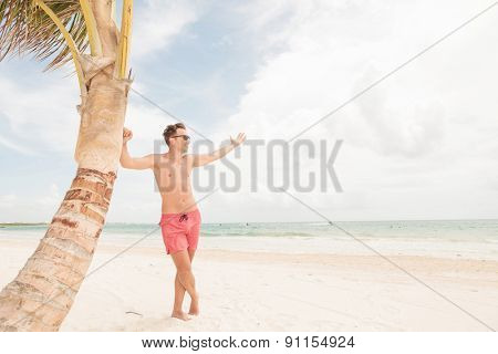 Smiling lifeguard leaning on a palm tree while holding his hand up.
