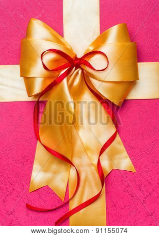 golden bow made from silk on pink background