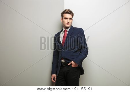 Pensive young business man holding one hand in his pocket while leaning on a grey wall.