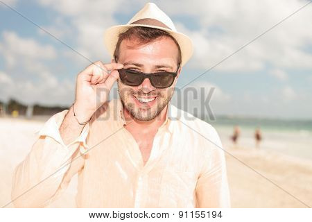 Portrait of a handsome young man fixing his sunglasses while smiling to the camera.