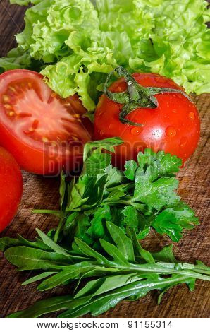 Juicy tomatoes with green-stuff on wooden table