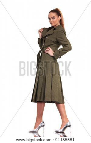 Side view of a elegant business woman walking on studio background while pulling her collar,