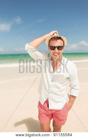 Happy young man walking on the beach holding his hand in pocket, smiling at the camera.