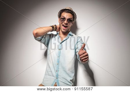 Hansome young fashion man leaning on a grey wall while showing the thumbs up gesture