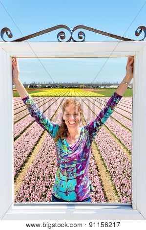 Woman in window near field of pink flowers