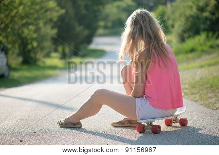 Blonde skateboarder woman resting outdoor