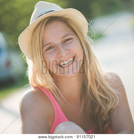 Summer girl portrait. Blonde woman smiling happy on sunny summer or spring day outside in park