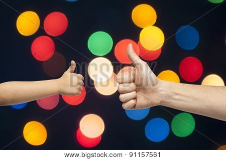 Father And Son Hands Giving Like On Christmas Lights Background