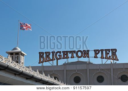 A Signage Of Brighton Pier With The English Flag