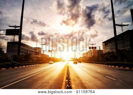 Empty road and buildings under sunset