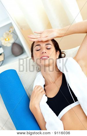 Tired Woman Sitting On A Sofa After Working Out In Her Living-room