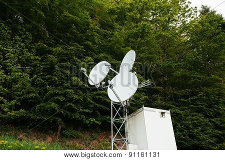 Three Satellite Dish On A Communication Tower In The Middle Of A Green Forest